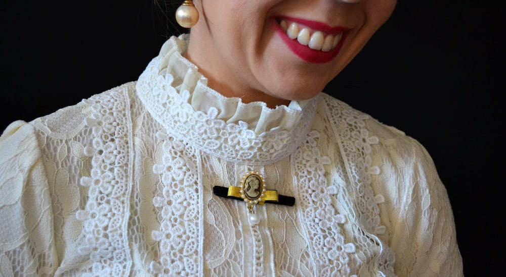 Smiling woman wearing a white lace blouse with cameo-shaped brooch.