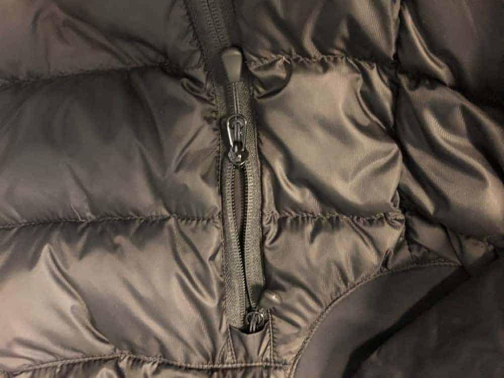A close up photo of Canada Goose side pocket zipper.