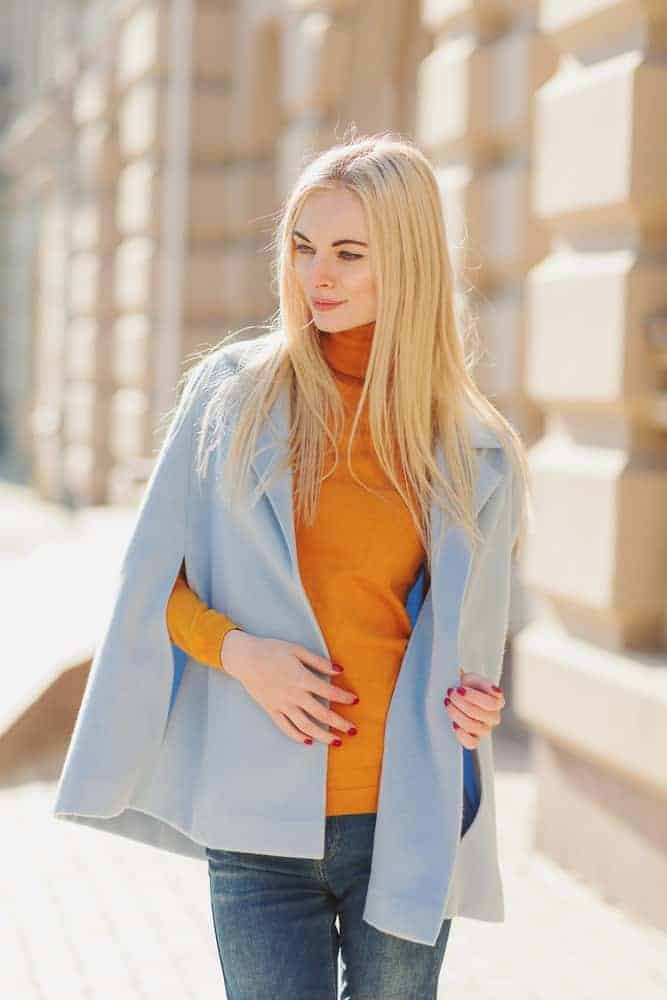 Woman wearing a blue cape sweater over an orange turtleneck long sleeves.
