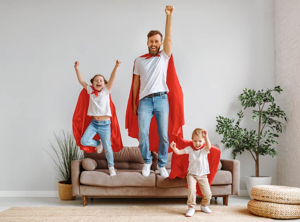 Father with two children in casual clothes and red superhero cloaks jumping from couch to floor.