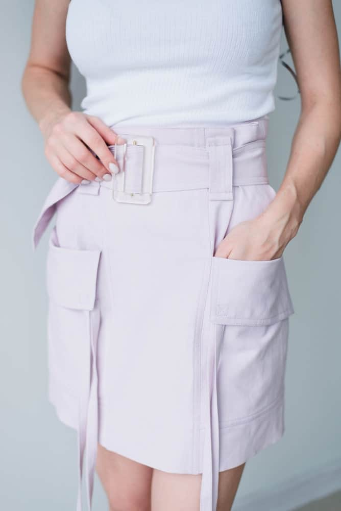 Woman wearing a white blouse and lilac cargo skirt.