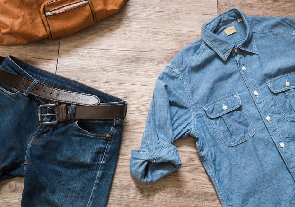 Blue chambray shirt and a denim jeans with a leather belt.