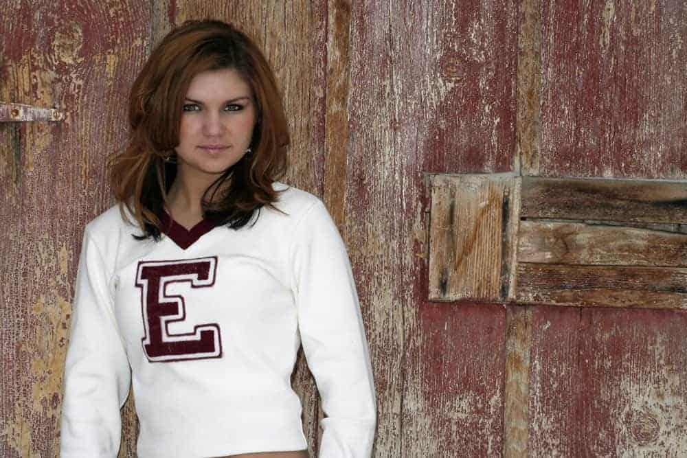 Teenage girl wearing a cheerleader sweater against a wooden background.