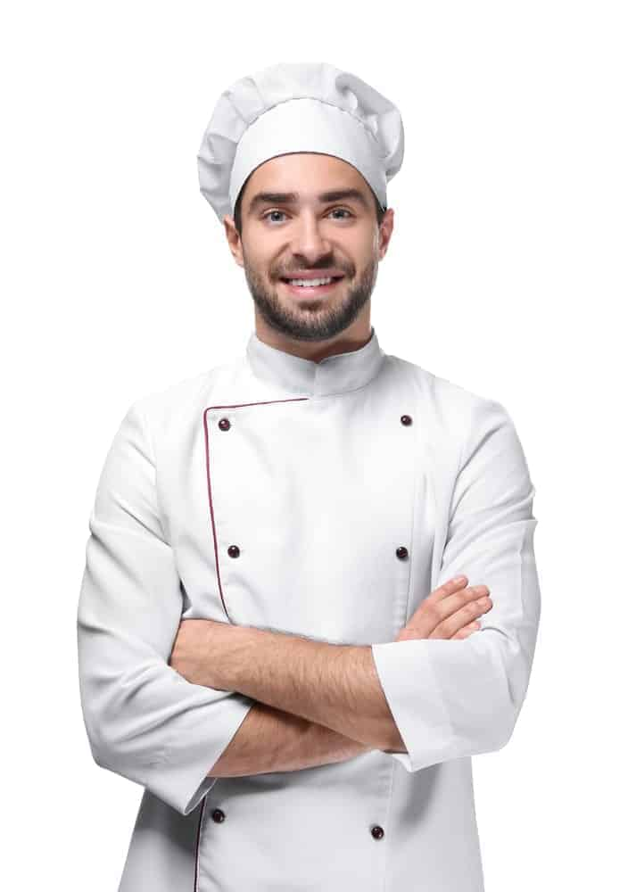 A chef folds his hands and smiles at the camera.