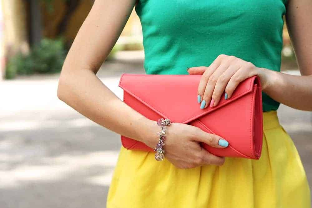 Woman in bright outfit with orange clutch bag.