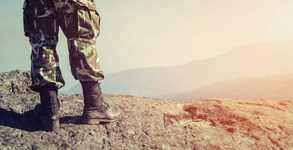 A soldier in uniform and combat shoes standing on the top of a mountain.