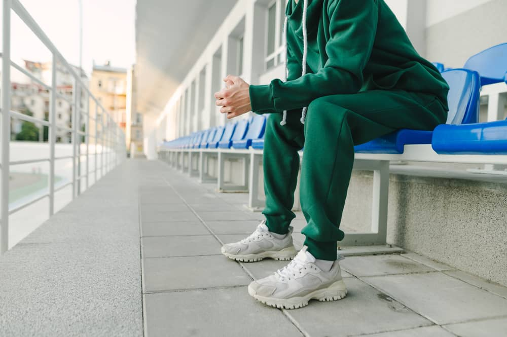 Man in green coordinates and white sneaker sitting on a blue chair.
