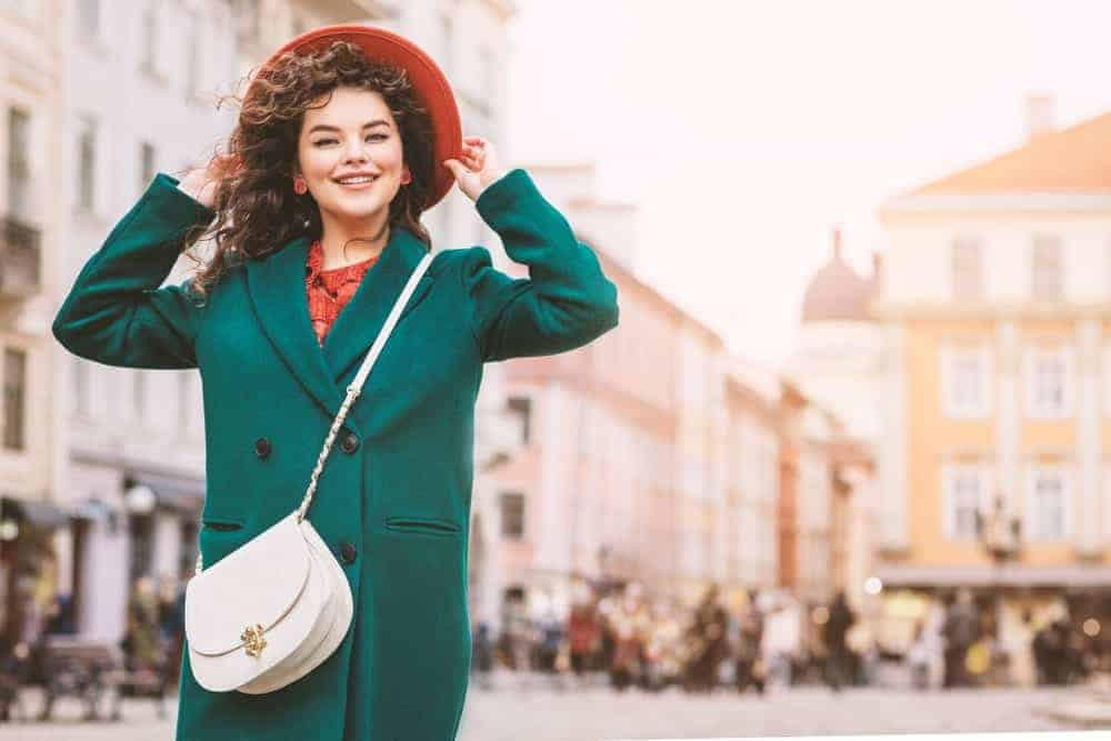 Lady in green coat with white crossbody bag.
