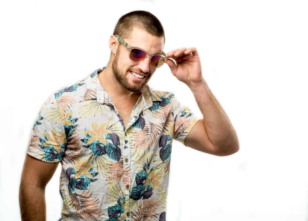 Man in a buzz cut wearing a sunglasses and a Cuban collar shirt.