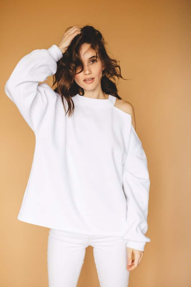 Woman in a white cutout sweater against a beige background.