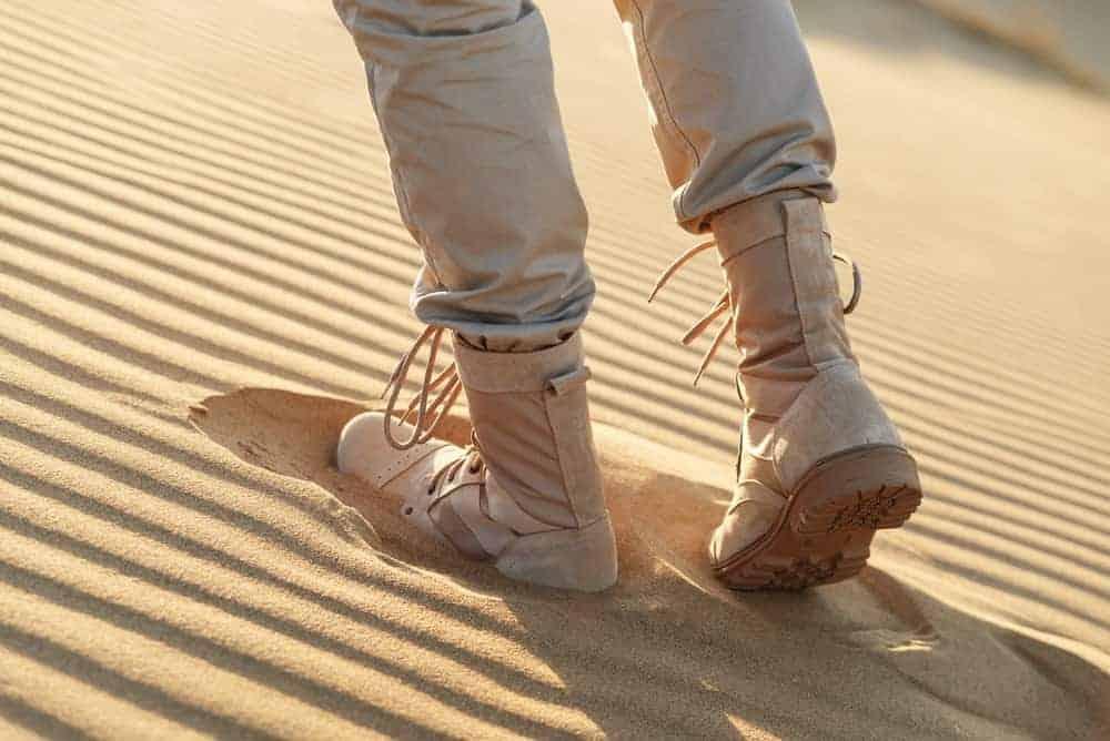 A man in beige boots walking through the desert.