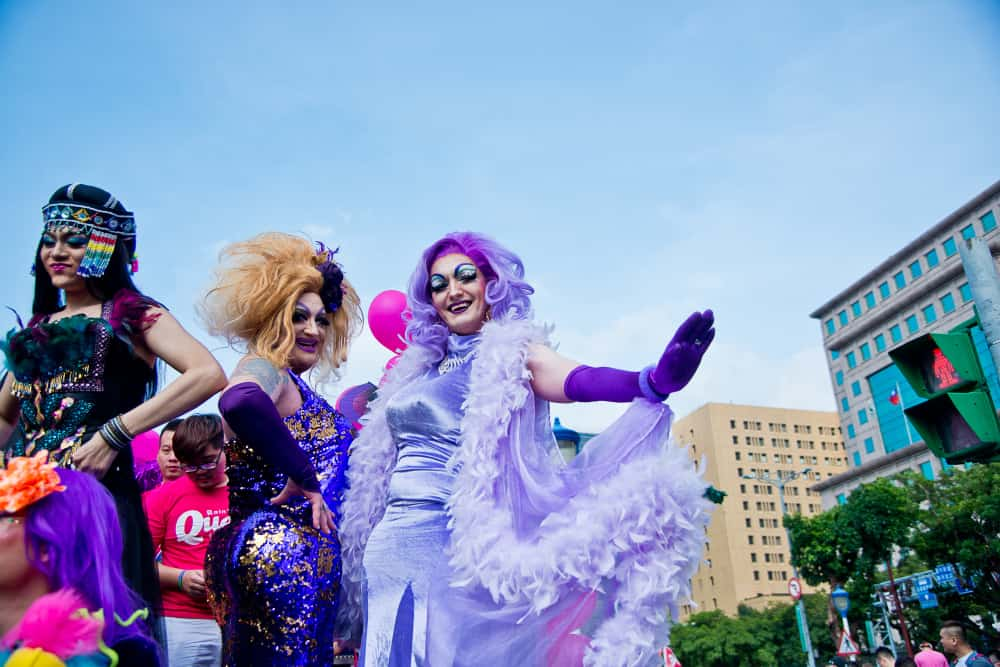 Drag queens wearing colorful dresses during an event.