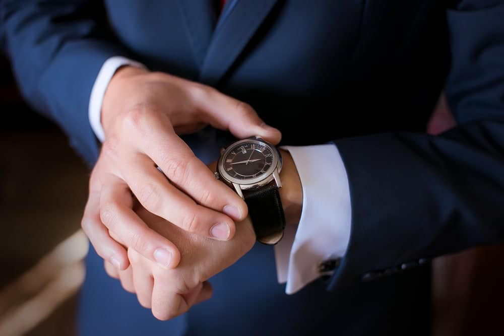 Groom in a wedding suit looking at his dress watch.