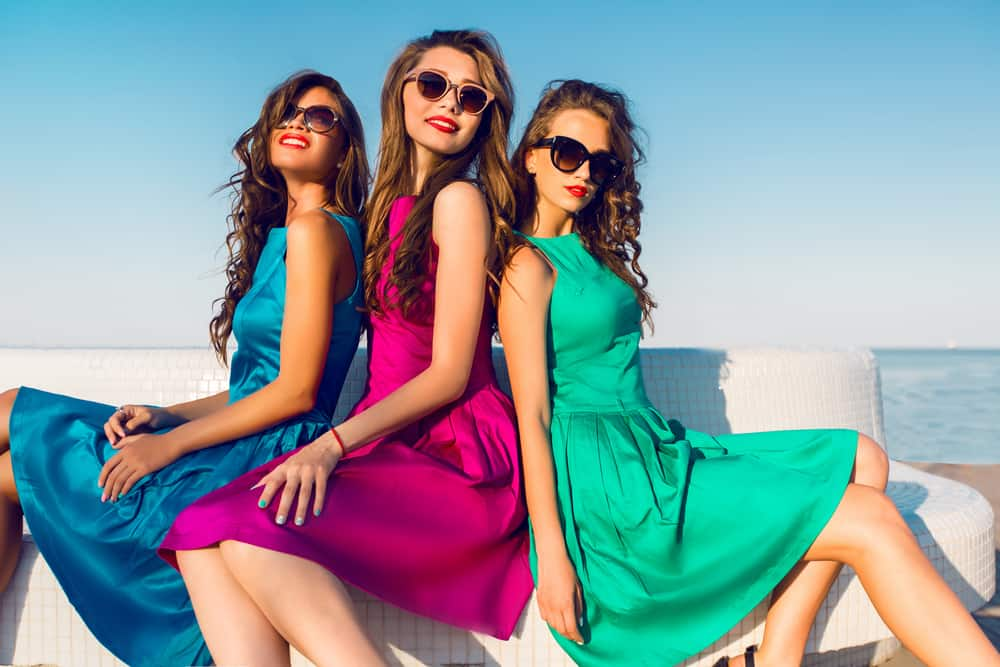 Three ladies in colorful dresses and shades pose near the beach.