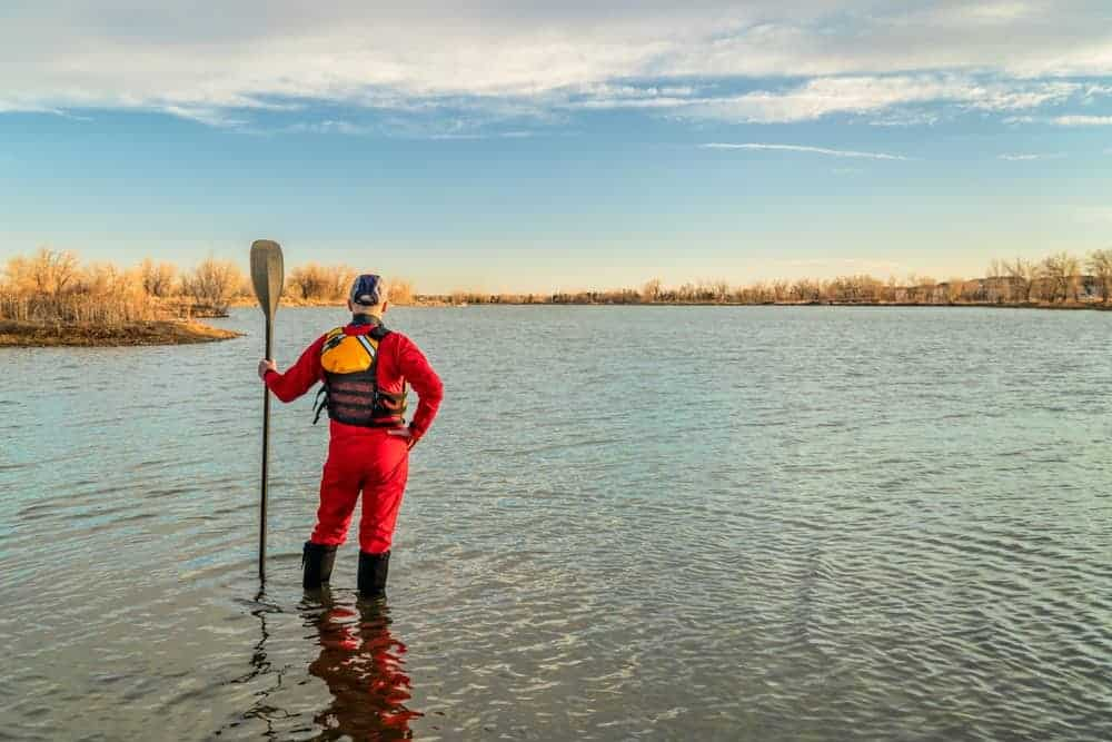 A man on a lake with paddle wearing a drysuit, lifejacket, and boots.