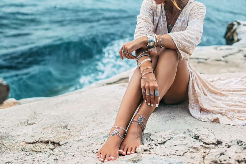Bohemian girl sitting by the seashore wearing silver jewelries.