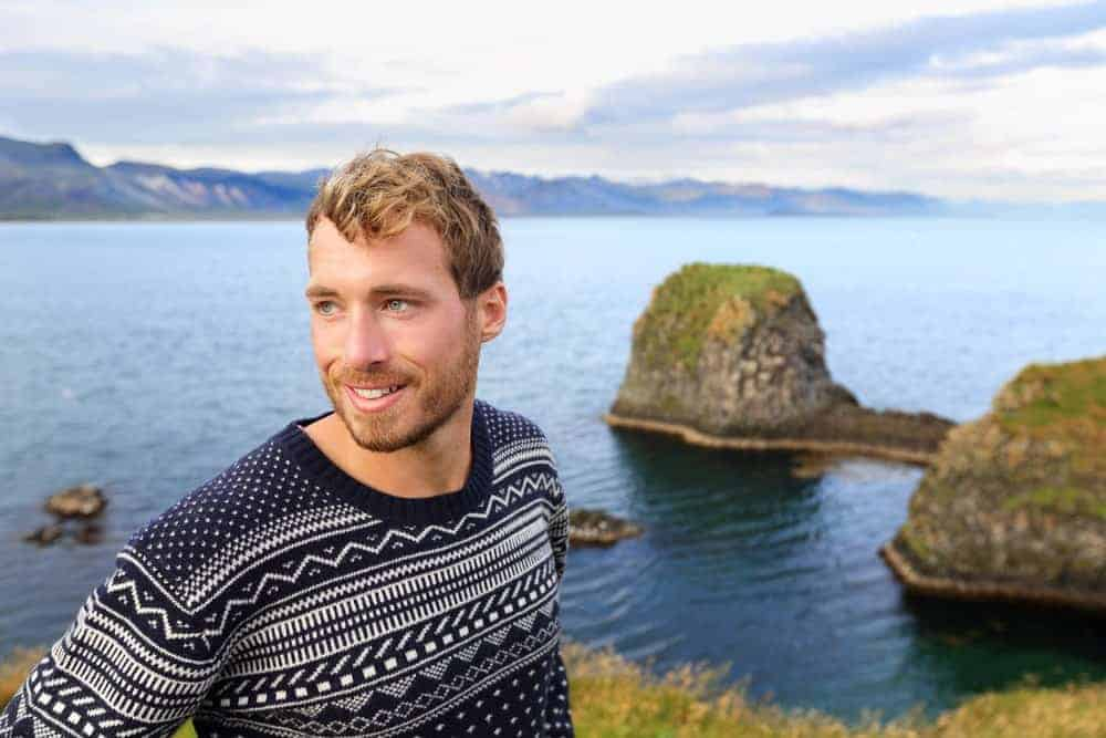Man in a fair isle sweater on a picturesque landscape.