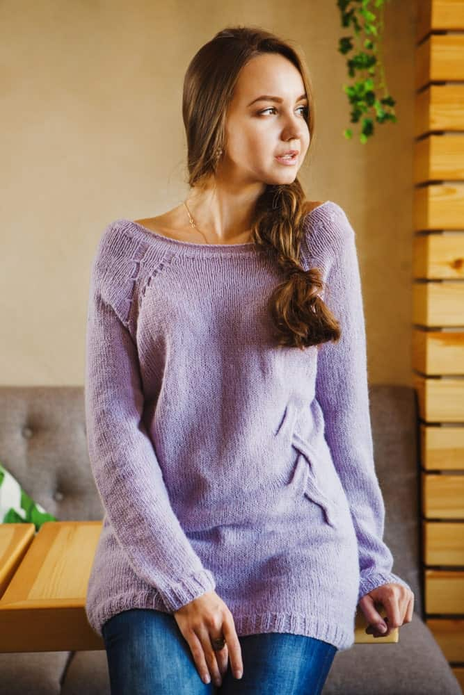 Woman in a purple fanny sweater sitting on a wooden table.