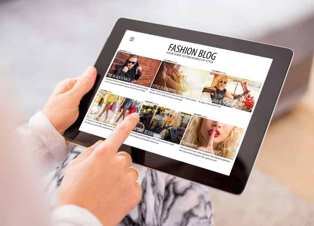 Swiping a tablet showing on screen a fashion blog.