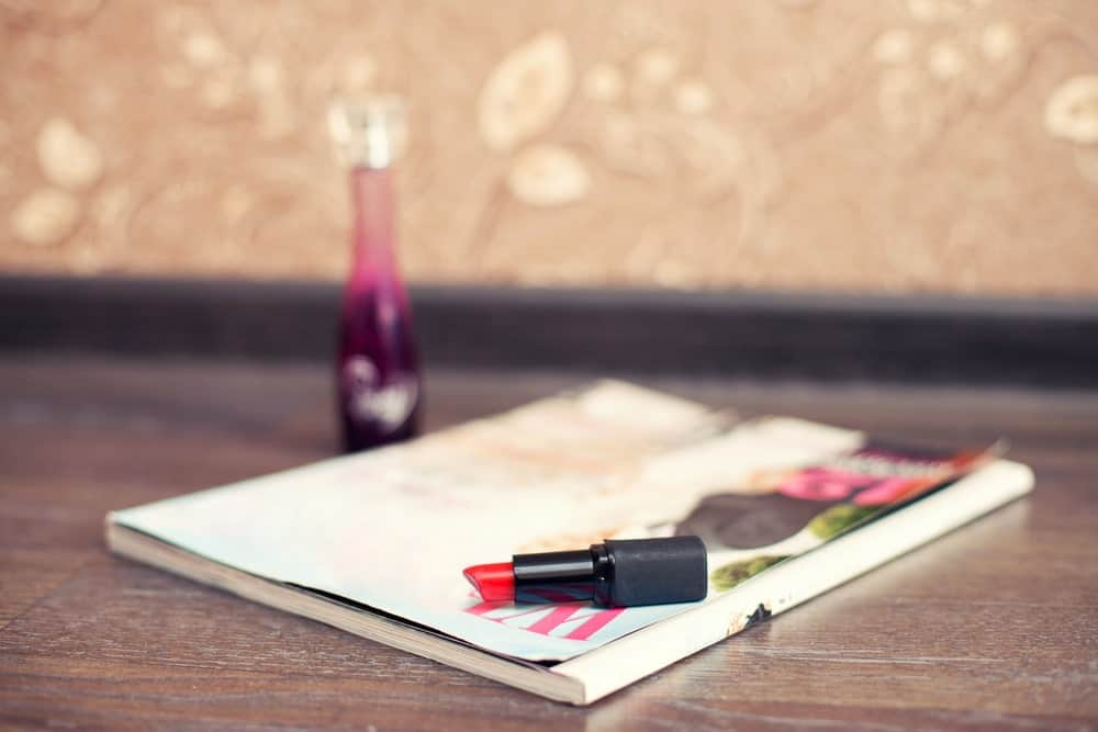 A red lipstick lying on a fashion book on a wooden desk.