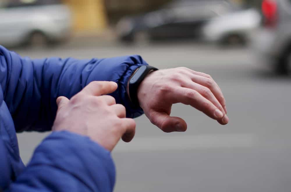 A cropped photo of a person looking at his fitness bracelet.