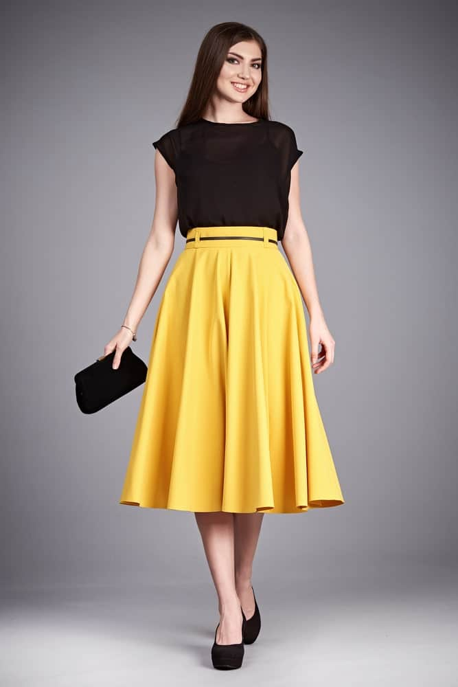 Woman in black blouse and yellow flared skirt.