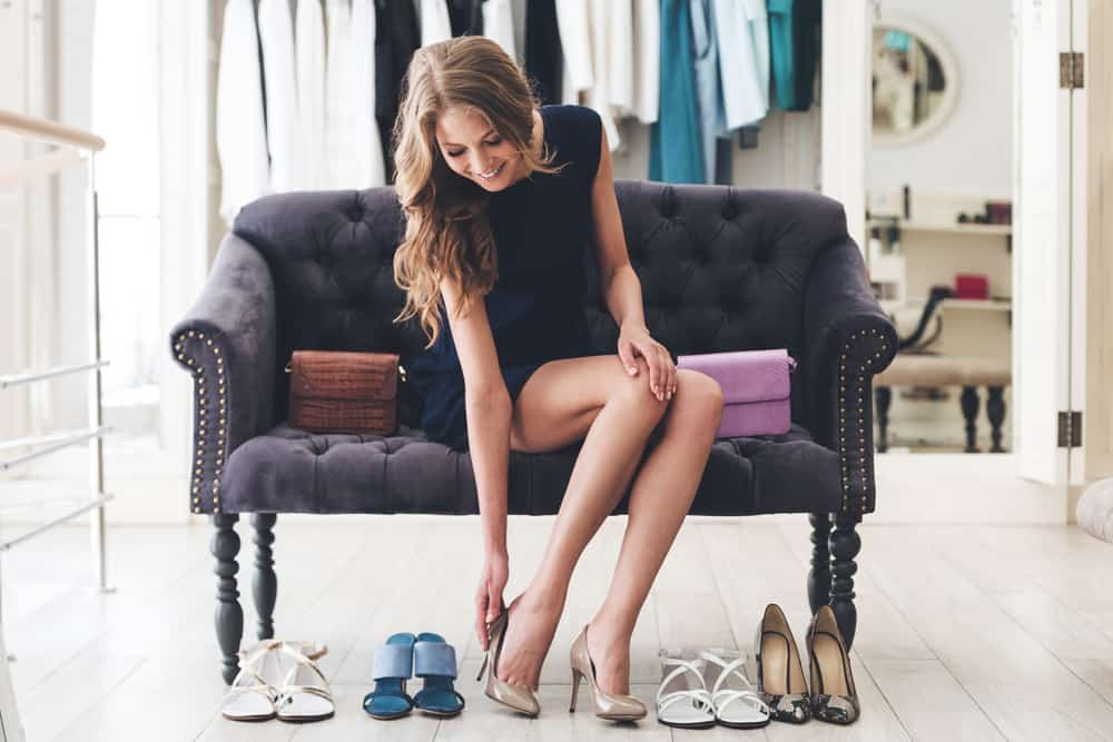 Woman trying on high heel shoes while sitting on sofa at the store.