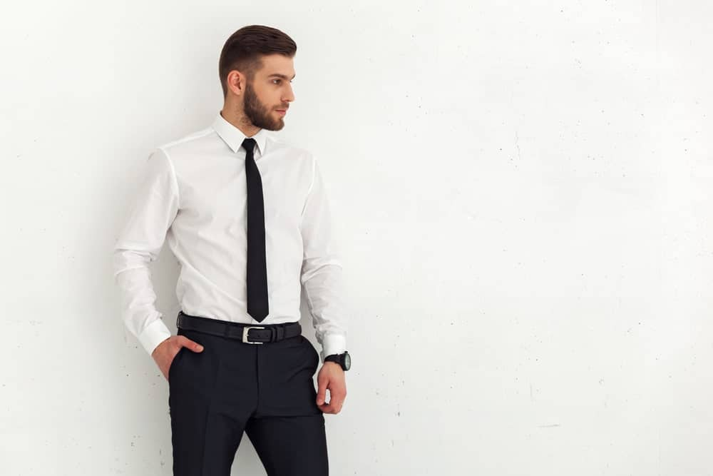 Bearded man in a white formal shirt and a black pants along with a black necktie.
