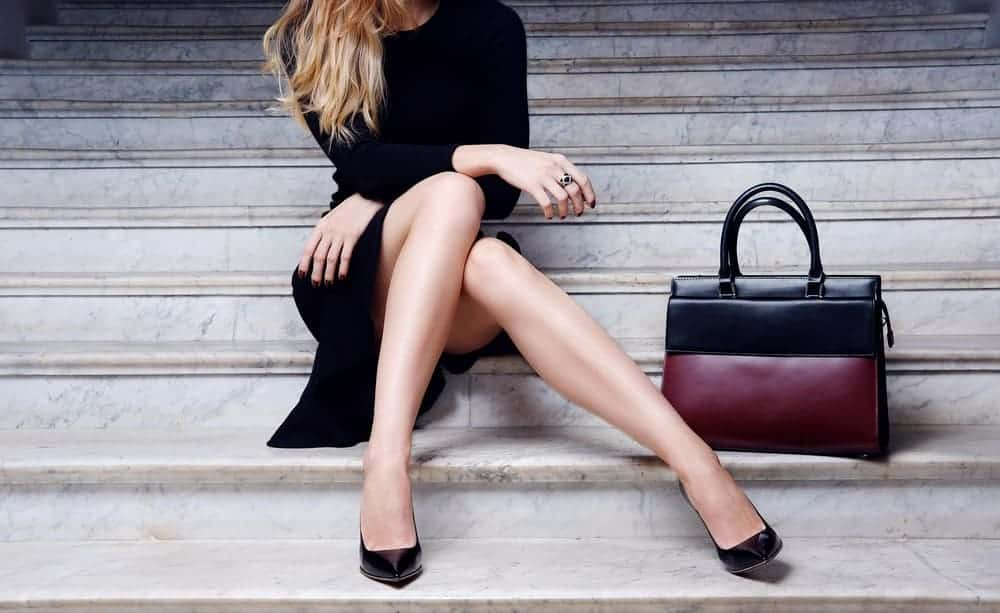 Woman sitting on marble stairs with a leather handbag on her side.