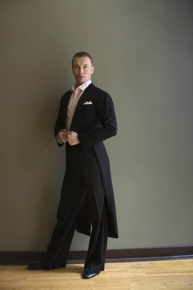 A man wearing frock coat stands against the wall.