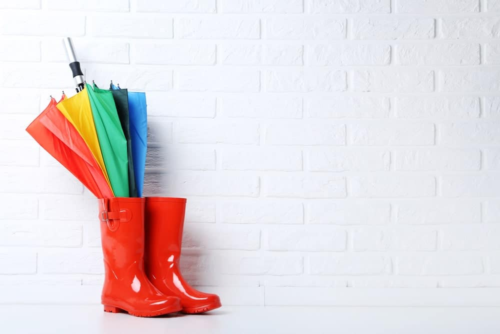Red galoshes boots with a multicolored umbrella against a brick background.