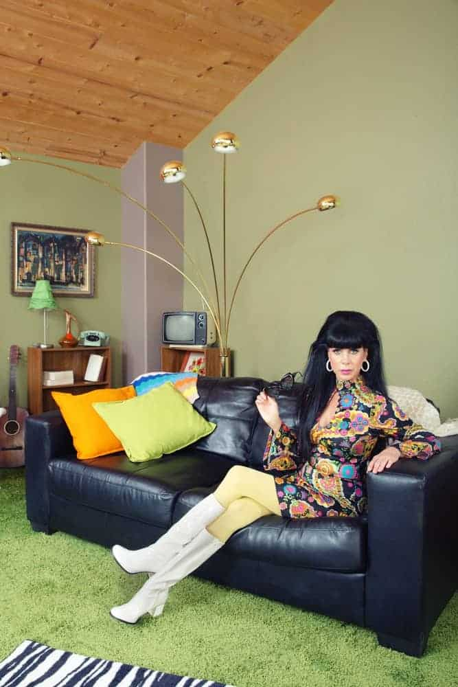 A woman in retro outfit and go-go boots sitting on a black leather sofa.