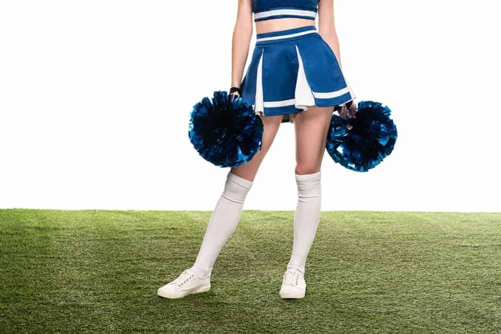 Cheerleader in a blue godet skirt holding pom poms.