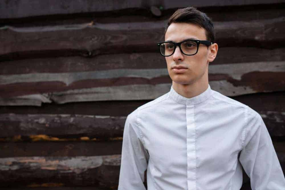 Young man wearing an eyeglasses in a white grandad collar shirt.