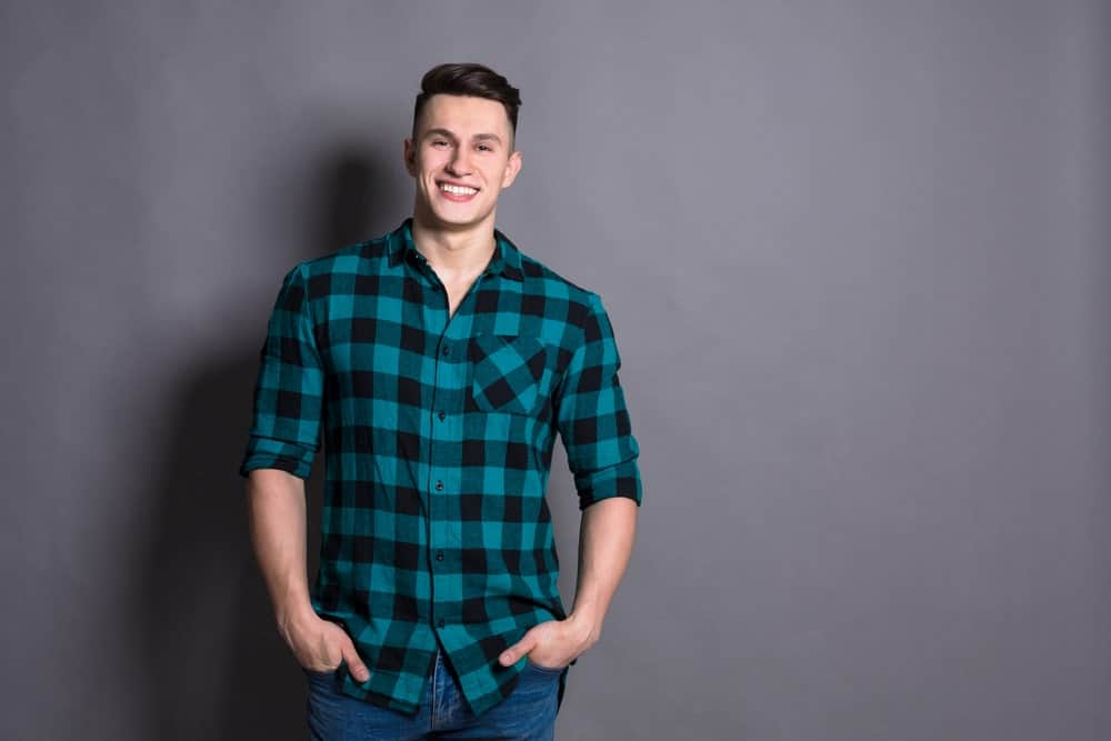 Young man in a green plaid shirt on a gray background.