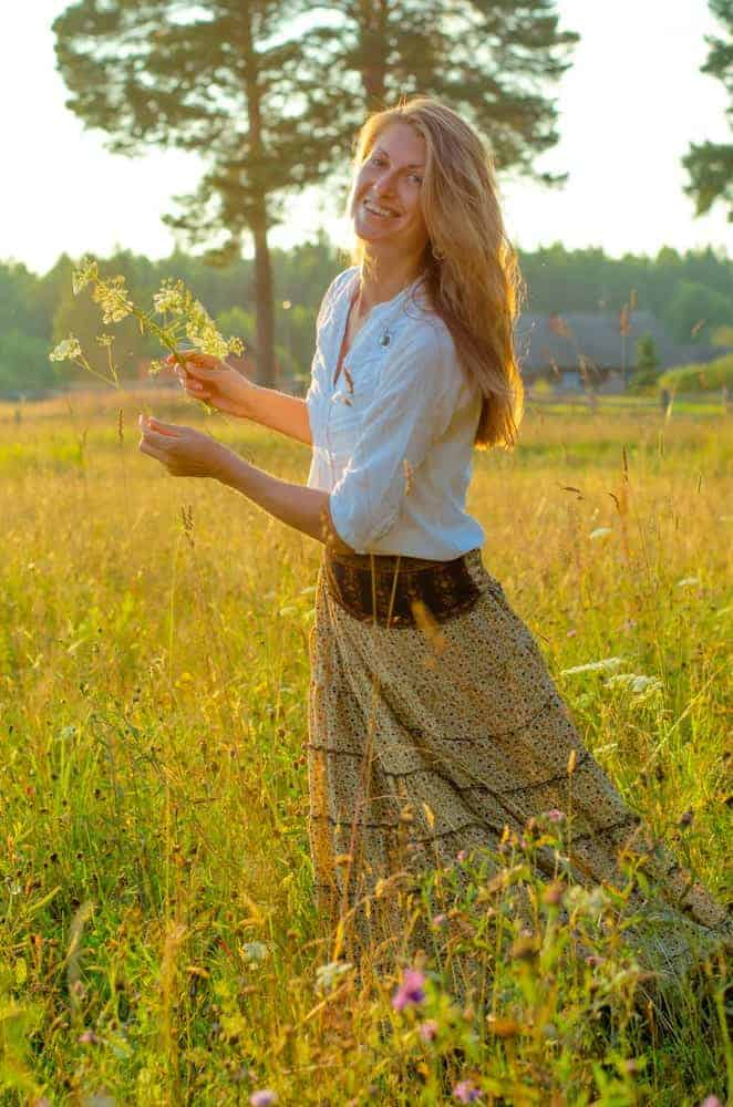 Woman wearing a white blouse and long yellow gypsy skirt.