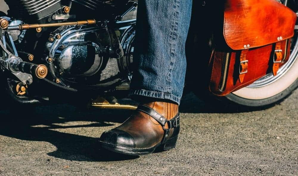 A biker on a retro chopper motorcycle wearing harness boots.