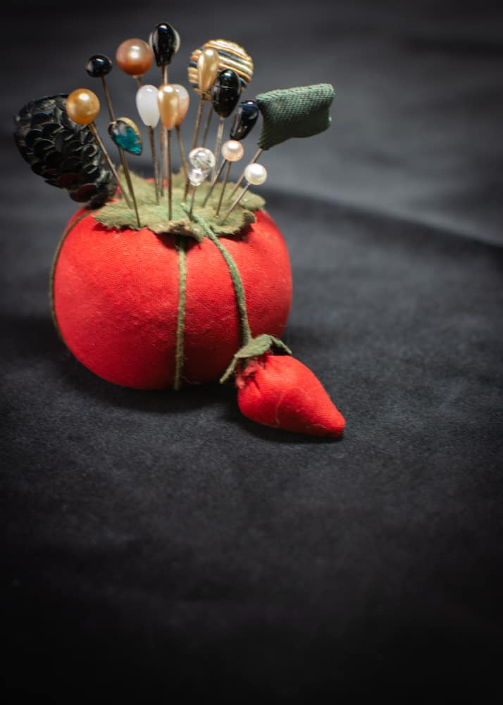 Red pin cushion with hatpin assortment.