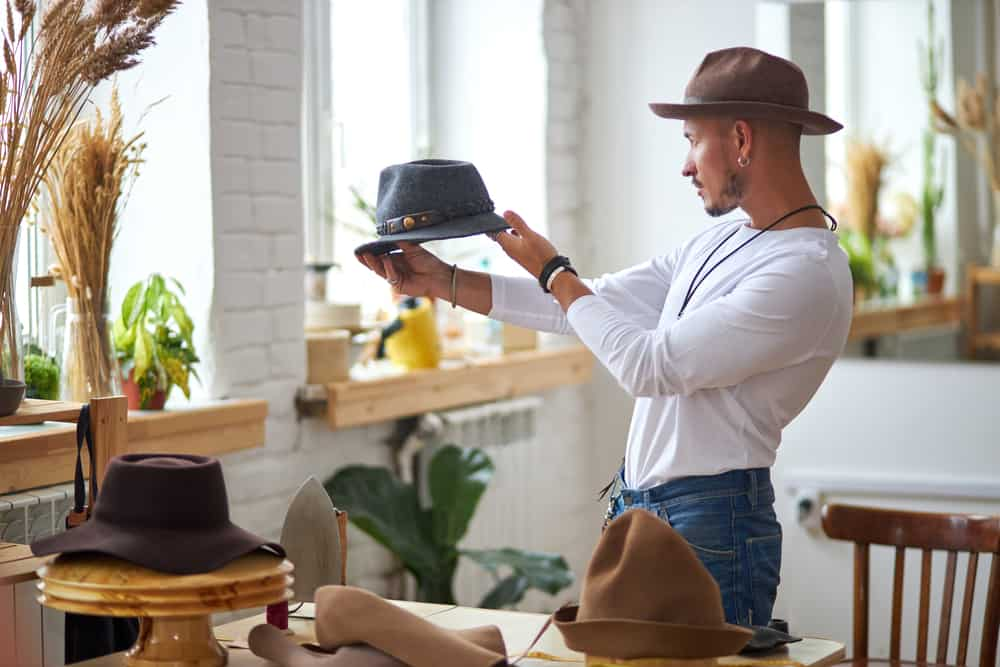 Man holding a hat in his workshop.