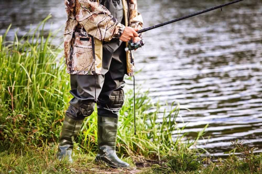 A man in hip boots fishing on the river bank.