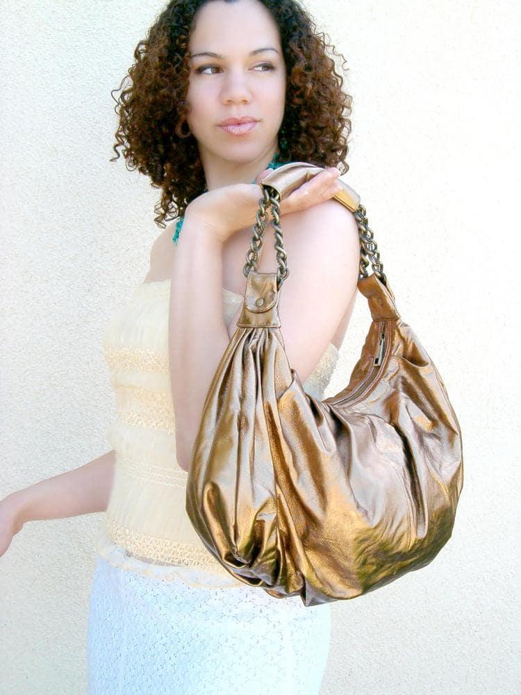 Women holding a metallic hobo handbag.