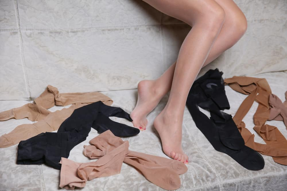 Woman legs in pantyhose and different new pairs of tights on the sofa.