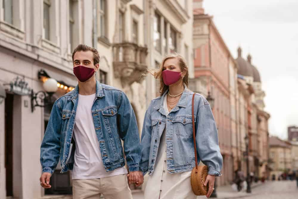 A couple in masks and denim jackets walking down the empty street.