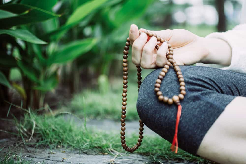 Close-up of female hand meditating and holding rosary.