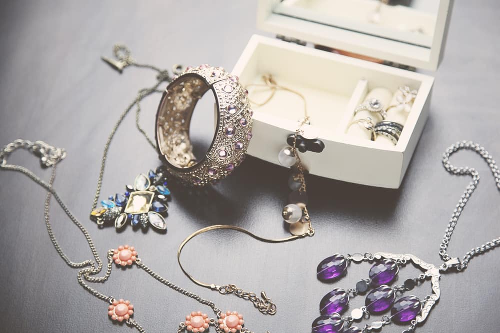 A collection of vintage jewelry in white jewelry box.