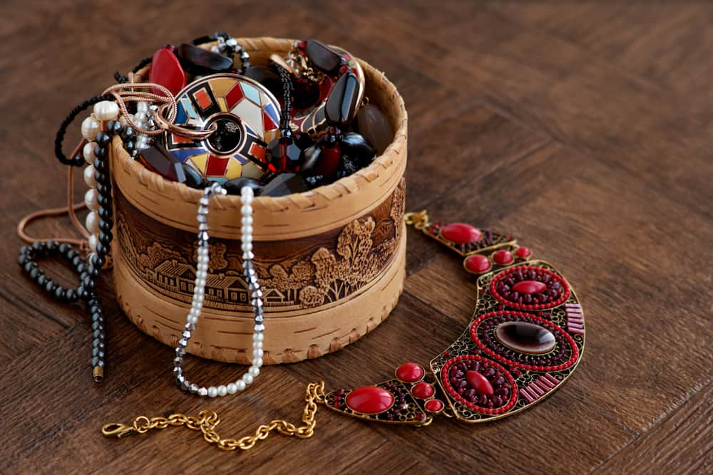 Various jewelries inside a round wooden box.