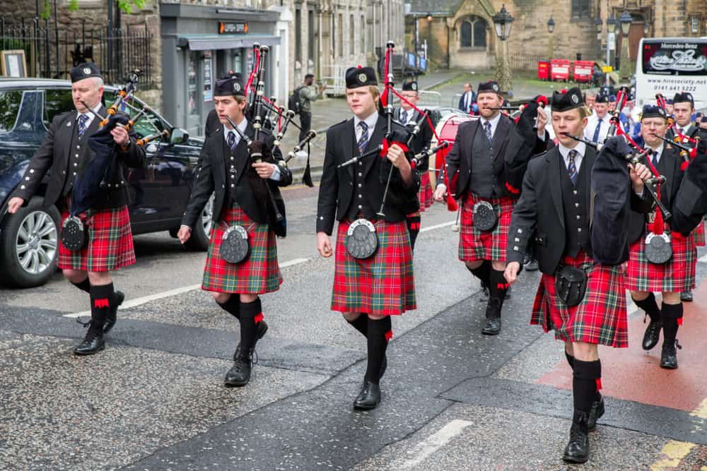 Ceremonial march of orchestra with bagpipes and kilts.