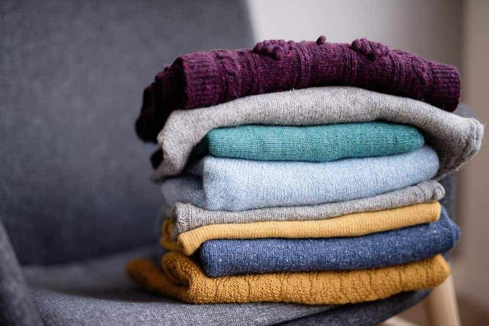 Knitted sweaters on pile above a gray chair.