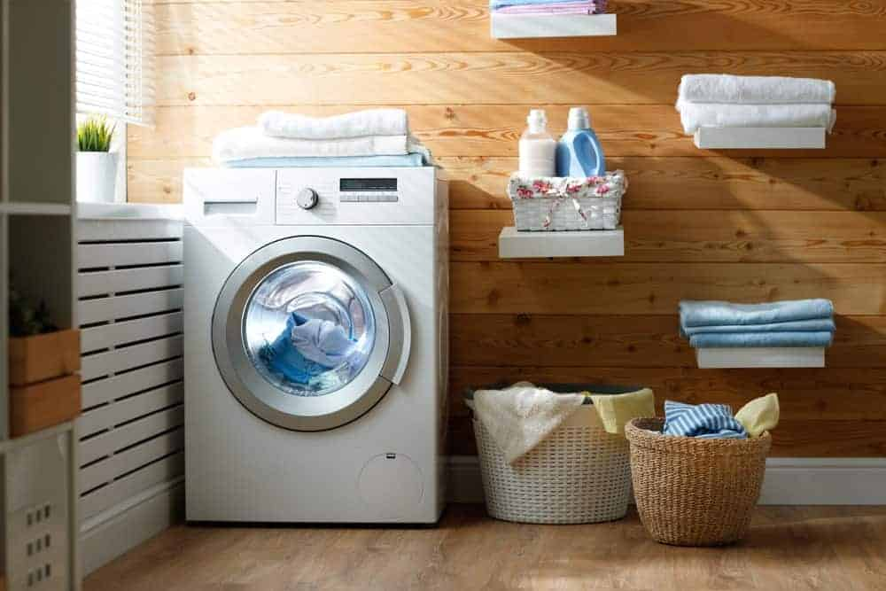 Laundry room with front load washing machine, floating white shelves, and wicker hampers.