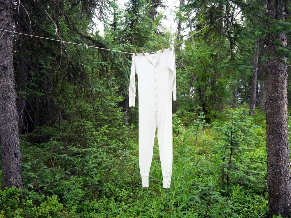 Long underwear hanging on clothesline between forest trees.